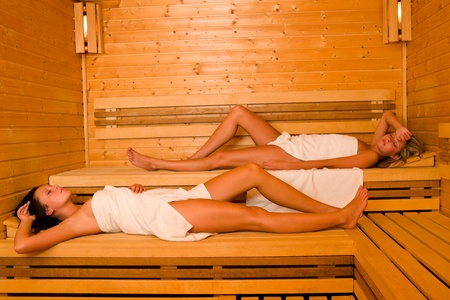 Sauna two healthy beautiful women relaxing lying wrapped in towel Stock Photo - 10459784