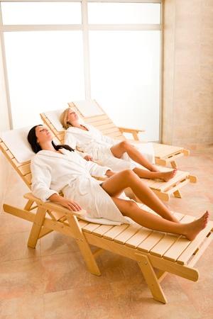 bathrobe: Spa luxury relax room two beautiful women lying on sun-beds