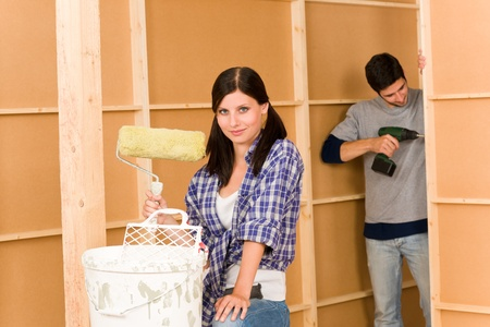 Home improvement: young happy couple fixing new house renovating wall Stock Photo - 10459781