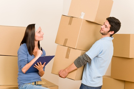 write off: Happy young couple moving into new home carrying cardboard boxes