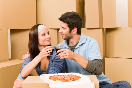 Moving into new home young happy couple have pizza lunch photo