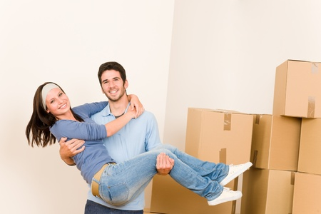 Moving new home young happy man holding woman cardboard boxes Stock Photo - 10459662