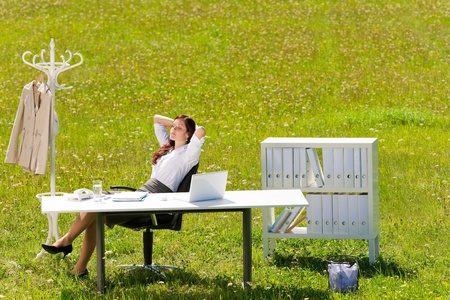Young businesswoman in sunny meadow nature office relaxing behind table Stock Photo
