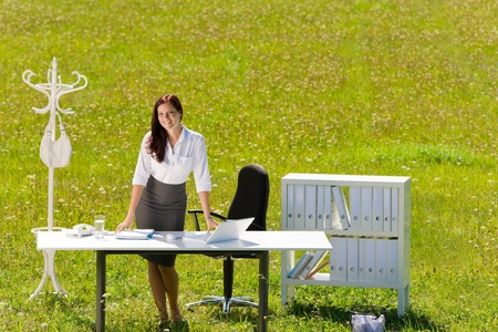 Young businesswoman in sunny meadow office smiling standing behind table
