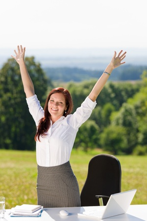 Businesswoman in sunny nature office hands up stretch behind table photo