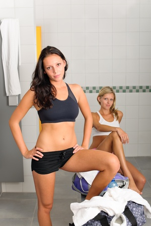 Locker room two sportive women getting ready fitness training equipment photo