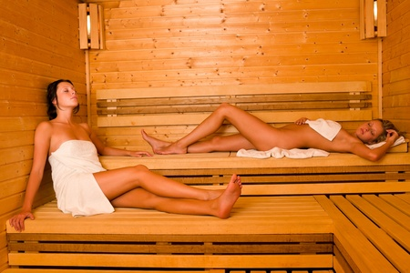 undressed: Sauna two healthy beautiful women relaxing lying wrapped in towel