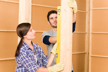 Verbetering van het huis lachende jonge paar bevestiging muur met waterpas