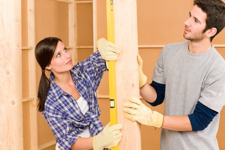 Home improvement smiling young couple fixing wall with spirit level photo