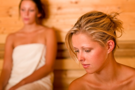 wrapped in a towel: Sauna two healthy beautiful women relaxing sweating covered towels