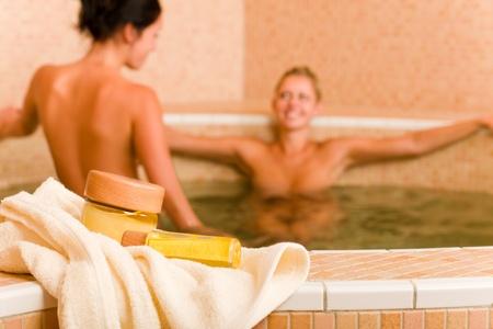 donne nude: Prodotti per il benessere e la bellezza di due donne nude all'interno salute bellezza acqua della piscina Archivio Fotografico