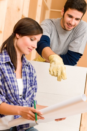 home improvements: Home improvement happy young couple with architectural blueprints fixing house