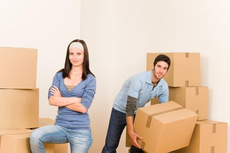 Happy young couple moving into new home carrying cardboard boxes Stock Photo - 10480355