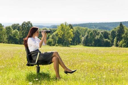 executive chair: Young businesswoman sit sunny meadow on armchair seeking binocular