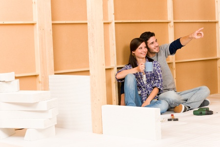 drill floor: Home improvement smiling young couple relax on floor building wall