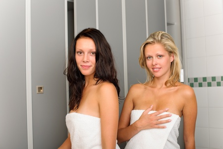 changing room: Locker room two relaxed women attractive wrapped in white towel Stock Photo