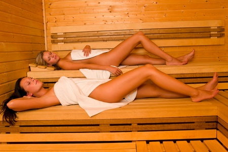 wrapped in a towel: Sauna two healthy beautiful women relaxing lying wrapped in towel