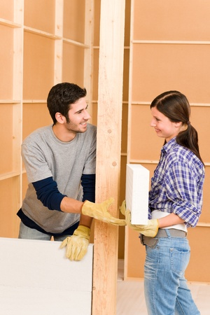 Home improvement smiling young couple building new brick panel wall photo