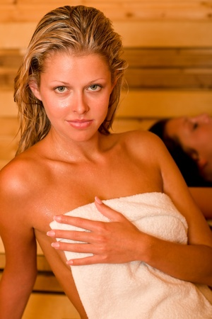 wrapped in a towel: Sauna two healthy beautiful women relaxing sweating lying covered towels Stock Photo