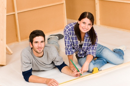 Home improvement young happy couple working on floor renovations photo