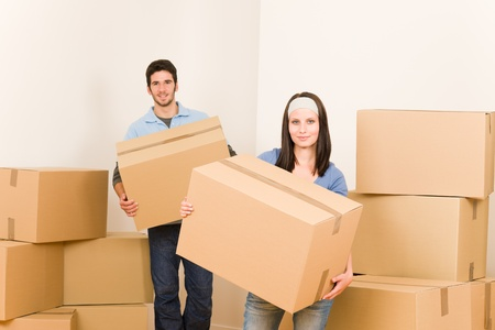 Happy young couple moving into new home carrying cardboard boxes photo