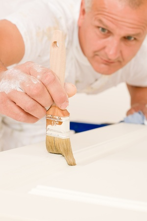 home decorating: Home decorating mature man painting white door with paint brush