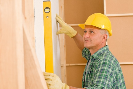 Mature professional handyman with spirit level working on home renovations photo