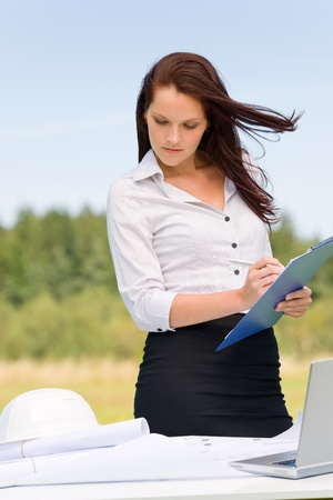 Young businesswoman attractive architect sunny nature write folder behind table Stock Photo - 10514597
