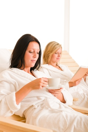 Beauty health spa treatment two women relax sun-beds coffee book photo
