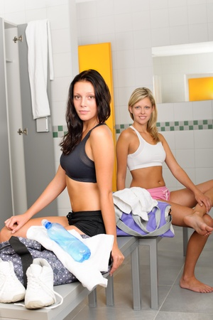 Locker room two sportive happy women sitting fitness training equipment photo