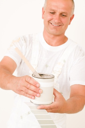 home decorating: Home decorating male painter with can of paint choosing color