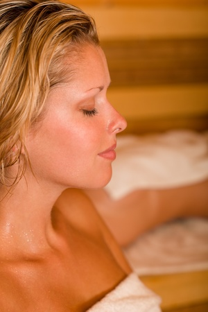 towels luxury: Sauna two healthy beautiful women relaxing sweating lying covered towels Stock Photo