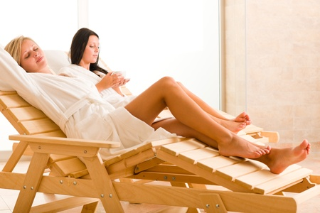 Two beautiful women relax sitting on sun-beds healthy luxury spa photo