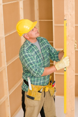 Handyman mature professional with spirit level working on home renovations photo