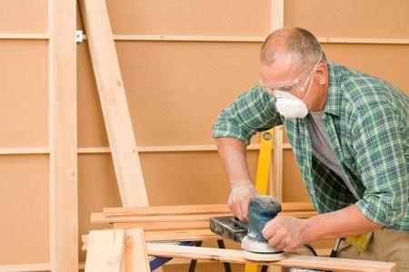 Handyman mature professional sanding wooden board diy new home renovation photo