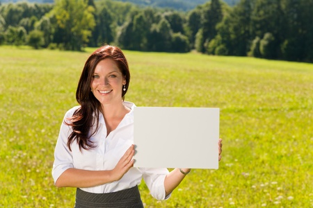Young businesswoman sunny meadow holding aside blank advertising banner photo