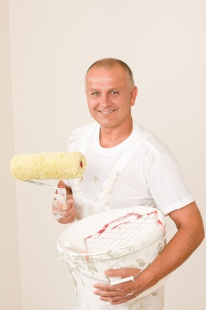 Home decorating mature man with paint roller, grid and bucket photo