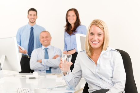 Business team pretty young businesswoman portrait with colleagues around table photo