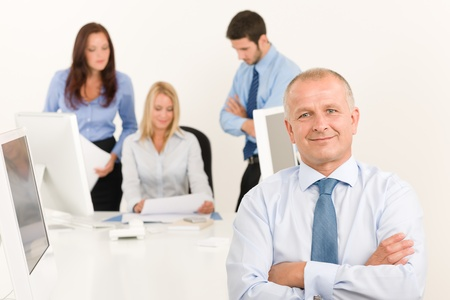Business team happy mature businessman with attractive colleagues looking files photo