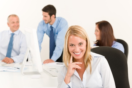 Business team pretty smiling businesswoman portrait happy colleagues around table photo