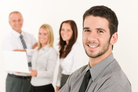 Business team handsome young man with colleagues posing in back Stock Photo