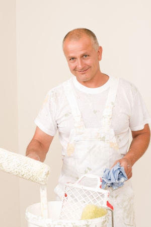 Home decorating mature man painting white wall with roller photo