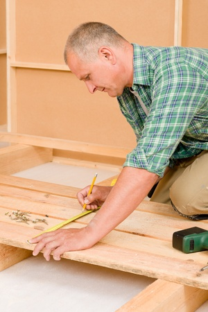 Mature handyman home improvement installing wooden floor in new house photo