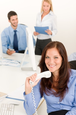 team management: Business team pretty businesswoman holding phone happy colleagues around table
