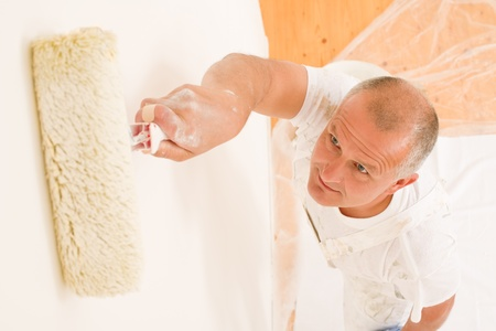Home decorating mature man painting white wall with paint roller Stock Photo