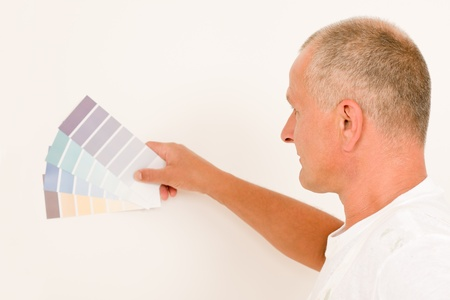 Home decorating mature male painter choose color swatches white wall photo