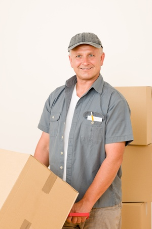 Friendly messenger or mover delivering parcel boxes on hand truck photo