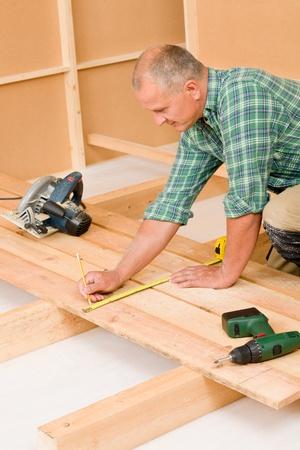 overhaul: Mature handyman home improvement installing wooden floor in new house