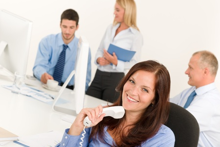 Business team pretty businesswoman holding phone happy colleagues around table photo