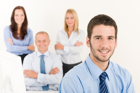 Business team close-up of young businessman with attractive happy colleagues photo